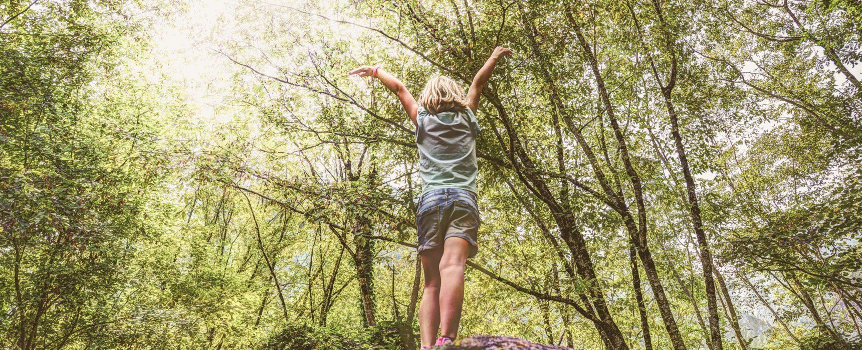 Kind steht glücklich im Wald.
