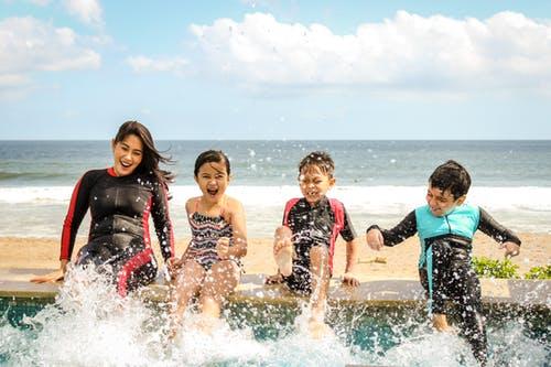 Am Strand planschen und baden die Kinder.